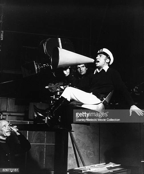 Actor and director Mel Brooks shouting through a bullhorn in costume on the set of the film 'Silent Movie' 1976