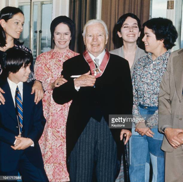 Actor and director Sir Charlie Chaplin with his family at the Savoy Hotel in London, after receiving a KBE, 4th March 1975. From left to right, his...