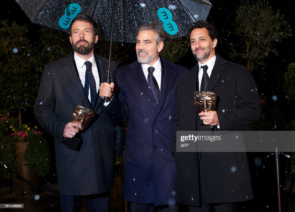 US actor and directors Ben Affleck and George Clooney and US actor Grant Heslov hold their awards as they pose arriving for the BAFTA British Academy Film Awards after party in London on February 10, 2013.