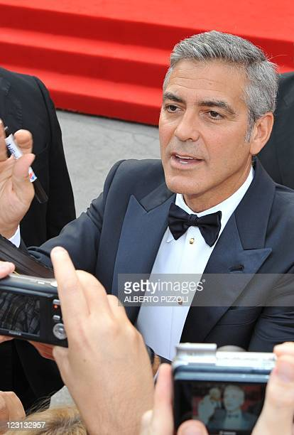 """Actor and film director George Clooney signs autographs as he arrives for the opening ceremony and the screening of """"The Ides of March"""" during the..."""