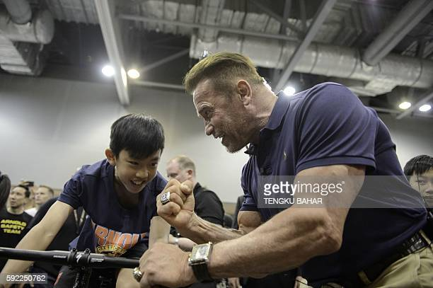 TOPSHOT US actor and former California governor Arnold Schwarzenegger cheers on a young participant on a stationary bicycle during the officiation of...