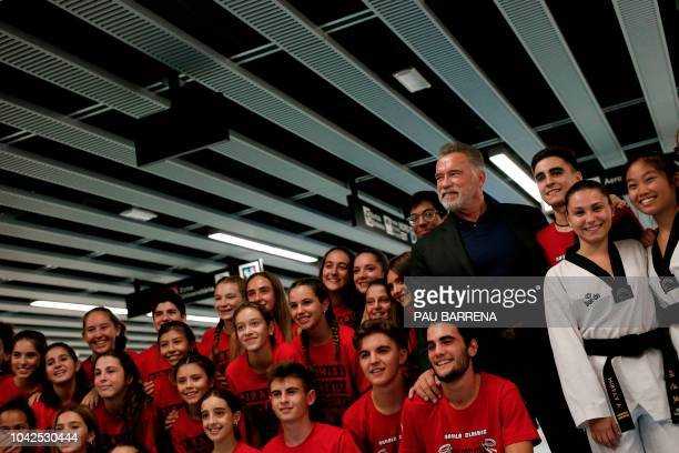 US actor and former governor of California Arnold Schwarzenegger poses with participants during a street marketing event ahead of the fitness and...