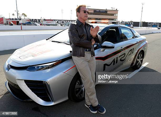 Actor and former governor of California Arnold Schwarzenegger poses with the 2016 Toyota Mirai pace car a hydrogen fuelcell electric vehicle on pit...