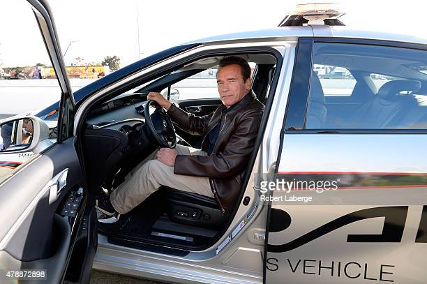 Actor and former governor of California Arnold Schwarzenegger poses in the 2016 Toyota Mirai pace car a hydrogen fuelcell electric vehicle on pit...