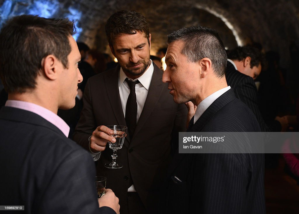 Actor and friend of the Roger Dubuis brand Gerard Butler (C) talks with CEO Jean-Marc Pontroue (R) at the Excalibur Dinner during the 23rd Salon International de la Haute Horlogerie at Caves des Vollandes on January 21, 2013 in Geneva, Switzerland.