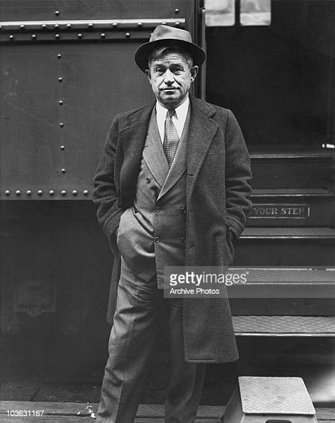 Actor and humourist Will Rogers pictured wearing an overcoat and hat as he stands beside the steps of a train USA circa 1925