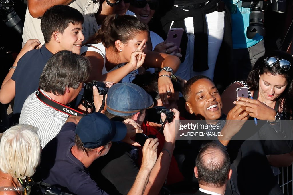 US actor and member of the Feature Film jury Will Smith poses for selfies with fans as he arrives on May 23, 2017 for the '70th Anniversary' ceremony of the Cannes Film Festival in Cannes, southern France. / AFP PHOTO / Laurent EMMANUEL