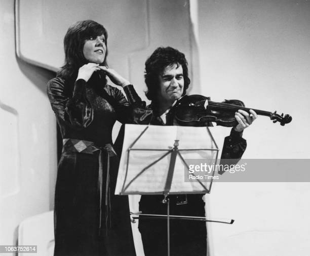 Actor and musician Dudley Moore playing a violin accompanied by singer Cilla Black during a television recording circa 1965