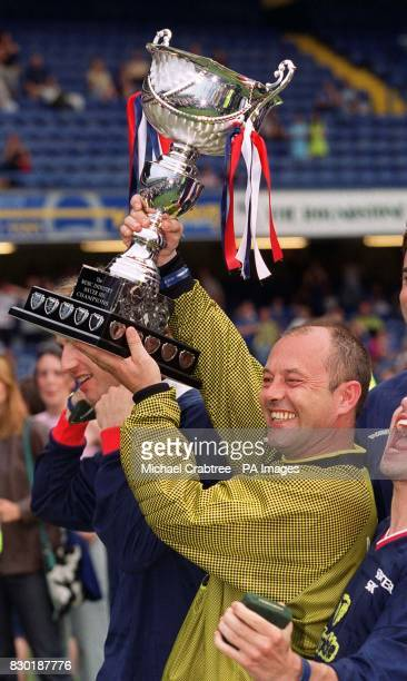 Actor and musician Keith Allen from the Fat Les team holds aloft the Music Industry Soccer Six trophy after his team won the Music Industry Soccer...