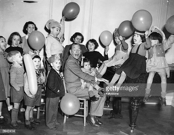 Actor and playwright Noel Coward playing the piano and singing at an orphanage in Chertsey where he officiated at the annual Christmas party Original...