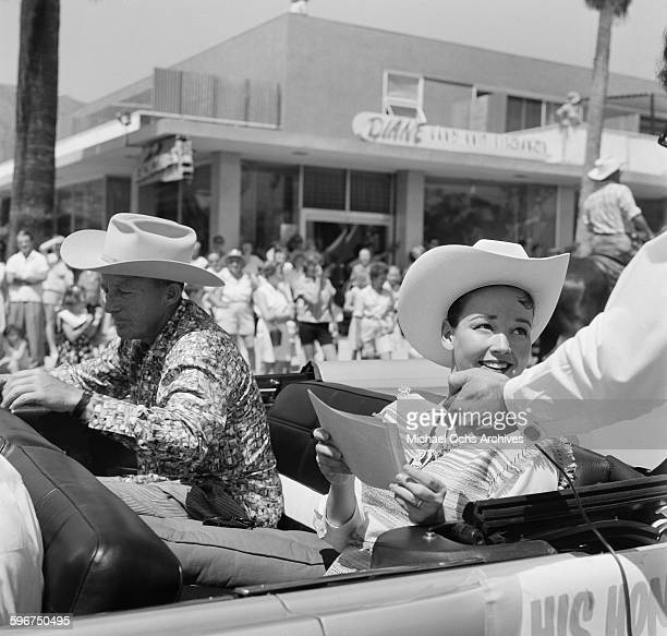 Actor and singer Bing Crosby and his wife Kathryn Crosby ride in a car during the 1958 Rose Parade in Pasadena California