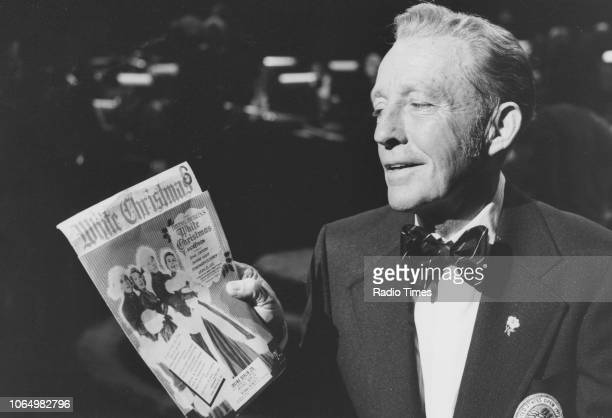 Actor and singer Bing Crosby pictured holding a poster for the film 'White Christmas' on the set of the television chat show 'Parkinson' July 18th...