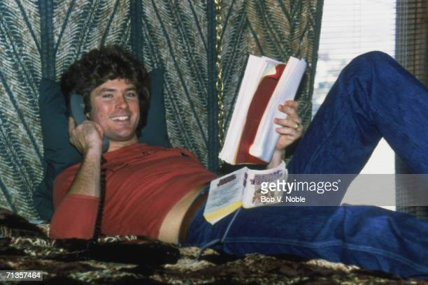 Actor and singer David Hasselhoff at home in Hollywood reading a script and an American football novel 'Semi Tough' while making a phone call 1979