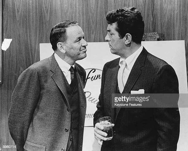 Actor and singer Frank Sinatra stares at fellow performer Dean Martin during filming
