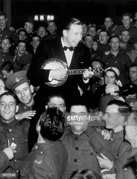 Actor and singer George Formby entertaining troops with his ukelele at a seaside concert hall in northern England