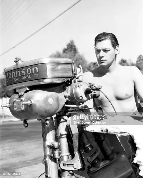Actor and swimmer Johnny Weissmuller who plays Edgar Rice Burroughs' hero Tarzan poses with a Johnson SeaHorse outboard motor on a speedboat circa...