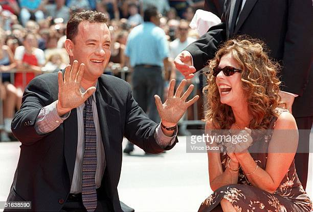 Actor and two time Oscar winner Tom Hanks laughs as he pulls his hands out of wet cement together with his wife, actress Rita Wilson during a hand...