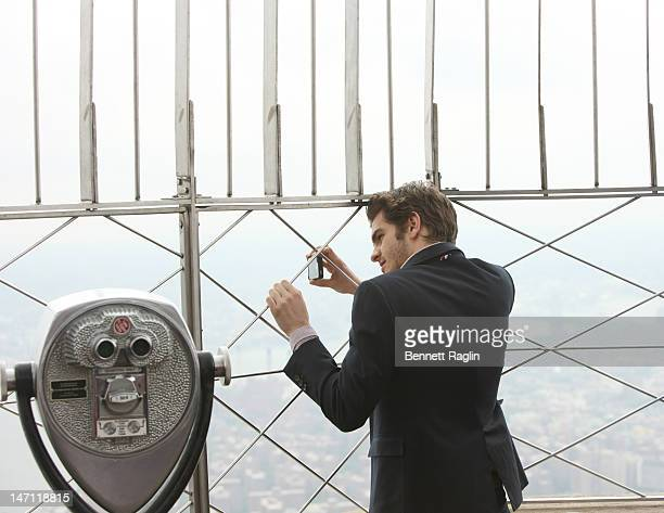 Actor Andrew Garfield takes a picture with his IPhone during a visit to The Empire State Building on June 25 2012 in New York City