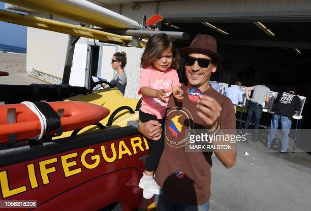 Actor Andrew Keegan shows his 'I Voted' sticker after voting with his daughter Aiya during the midterm elections at the Venice Beach Lifeguard...