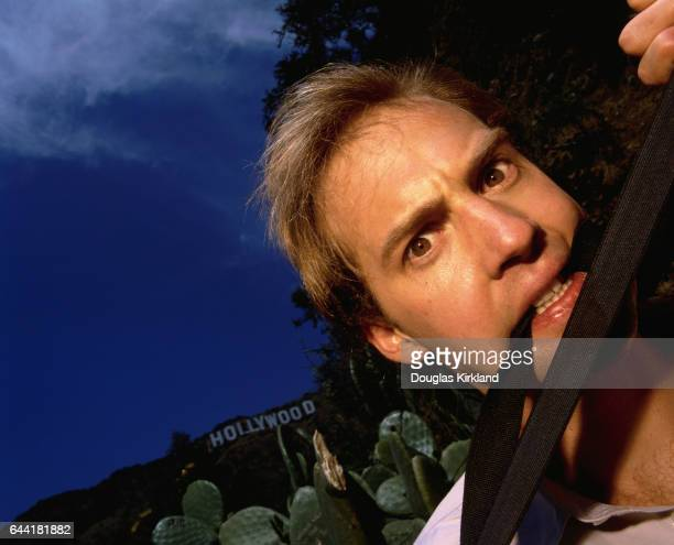 Actor Anthony Edwards chews on a pair of suspenders near the Hollywood Sign