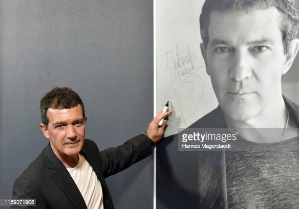 Actor Antonio Banderas poses in front of a portrait of him during the CineMerit Gala for Antonio Banderas during the Munich Film Festival at Gasteig...