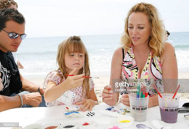 MALIBU CA AUGUST 25 Actor Antonio Sabato with daughter Mina Sabato and Actress Virginia Madsen paint shells on the beach at the French Connection's...