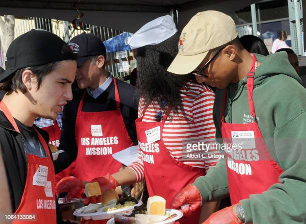 Actor Aramis Knight and musician Pharrell Williams attend the Los Angeles Mission hosts Thanksgiving Event for the Homeless held at Los Angeles...