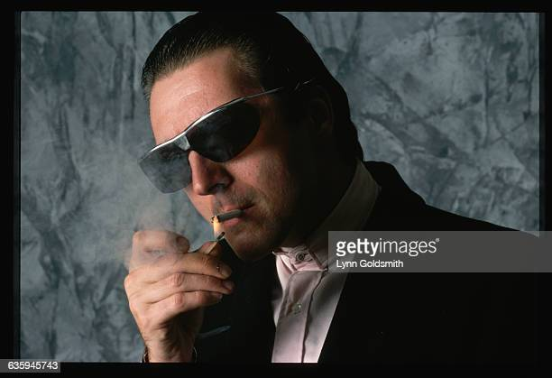 Actor Armand Assante wears dark sunglasses and lights a cigarette