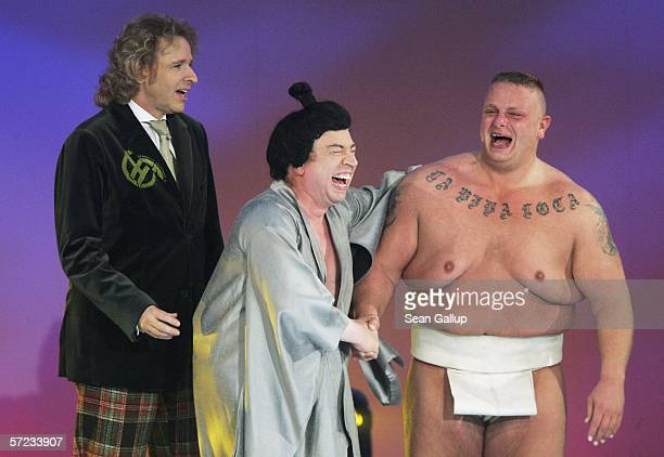 Actor Armin Rohde jokes with his challenger after fighting a sumo wrestling match while television host Thomas Gottchalk looks on at the talk and...