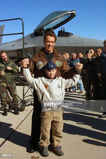 Actor Arnold Schwarzenegger and his son, Patrick, pose in front of an F-22 Raptor with airmen in this undated recent photo at Edwards Air Force Base...