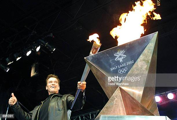 Actor Arnold Schwarzenegger passes the Olympic Flame to the cauldron at Universal City Walk during the 2002 Salt Lake Olympic Torch Relay January 15,...