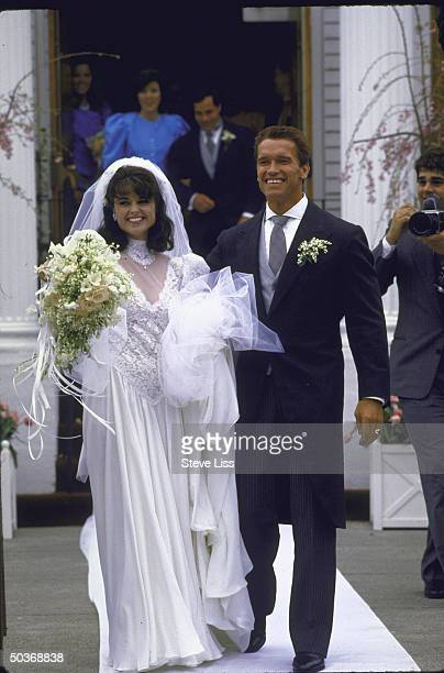 Actor Arnold Schwarzenegger with his new wife Maria Shriver Schwarzenegger on their wedding day standing in front of St Francis Xaviers Church
