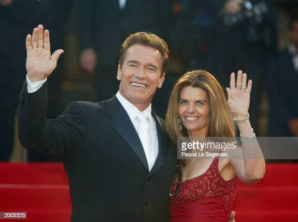 Actor Arnold Schwarzenegger with his wife Maria Shriver wave to fans as the couple arrives for the screening of the film 'Les Egares' at the Palais...