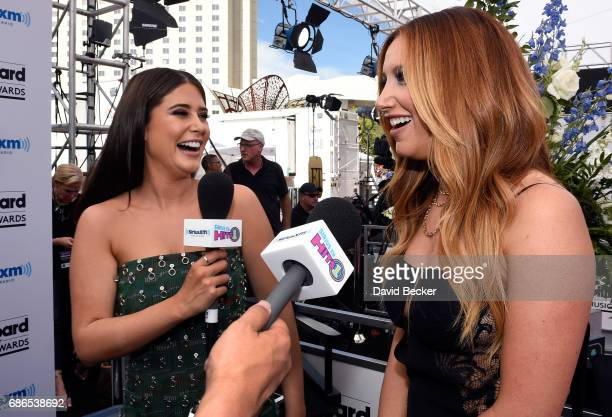 Actor Ashley Tisdale is interviewed by SiriusXM host Symon on SiriusXM's 'Hits 1 in Hollywood' on the red carpet leading up to the Billboard Music...