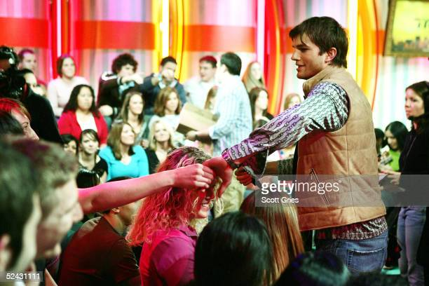 Actor Ashton Kutcher greets the audience during his visit to MTV's Total Request Live at the MTV Times Square Studios March 15 2005 in New York City