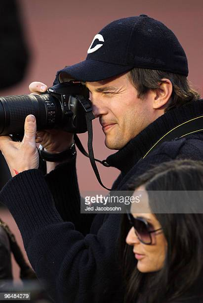 Actor Ashton Kutcher takes pictures from the sidelines with actress Demi Moore prior to Super Bowl XLIV between the Indianapolis Colts and the New...