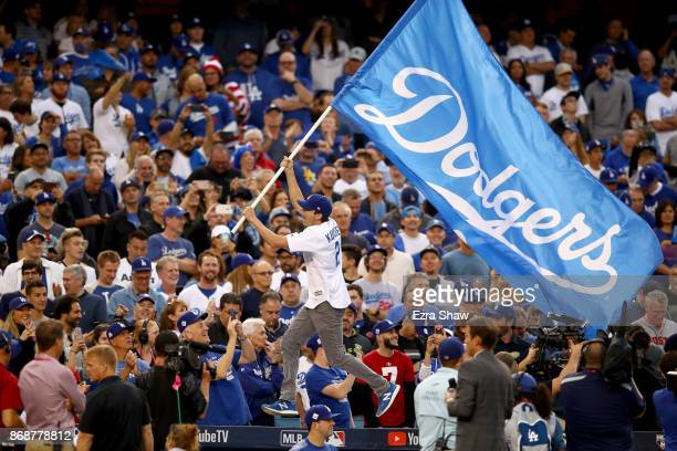 Actor Ashton Kutcher waves a Los Angeles Dodgers flag before game six of the 2017 World Series between the Houston Astros and the Los Angeles Dodgers...