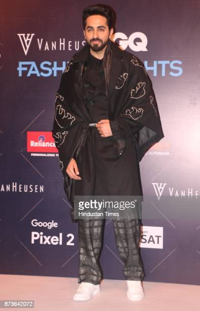 Actor Ayushmann Khurrana poses in checkered woollen pyjamas and a classic black overcoat with an animal motif stole from HiBearNation collection...