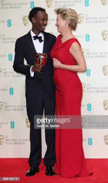 Actor Barkhad Abdi poses with actress Emma Thompson after she presented him with his Supporting Actor Award in the winners room at the EE British...