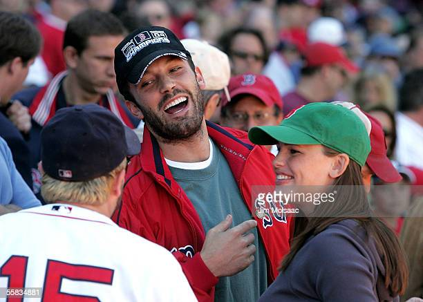 Actor Ben Affleck and wife actress Jennifer Garner laugh with player Kevin Millar of the Boston Red Sox prior to the start of the game against the...