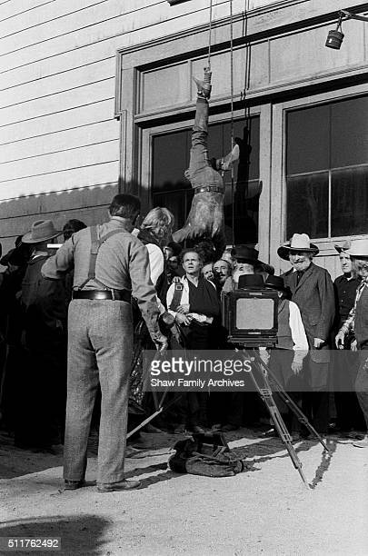 Actor Ben Johnson hangs from a noose tied around his ankle above the cast and crew while filming a scene that does not appear in the final edit of...