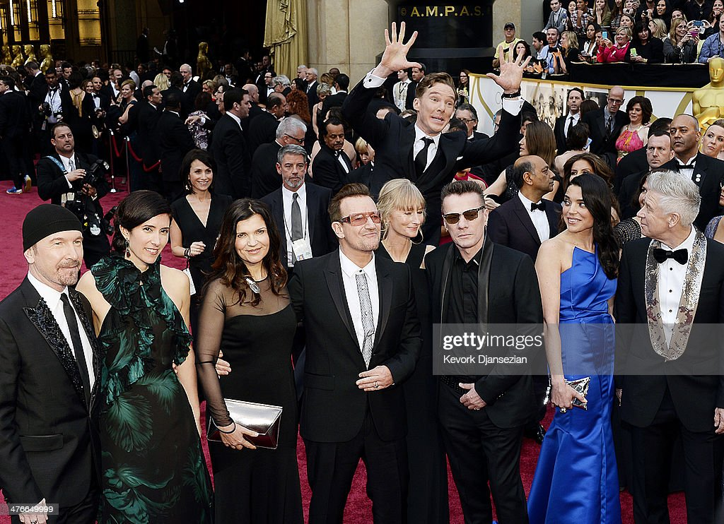 Actor Benedict Cumberbatch photo bombs the group photo of (L-R) musicians The Edge, Bono, Larry Mullen, Jr. and Adam Clayton of U2 as they arrive for the 86th Annual Academy Awards held at Hollywood & Highland Center on March 2, 2014 in Hollywood, California.