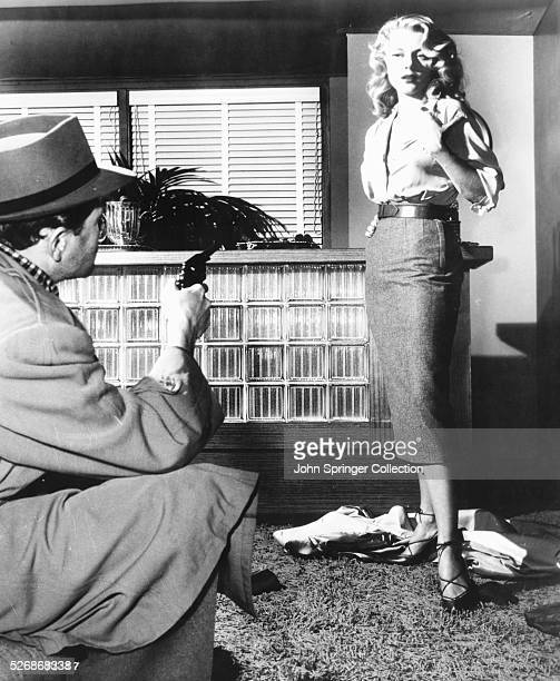 Actor Biff Elliot points a gun at actress Peggie Castle in a scene from the 1953 film I the Jury Elliot stars as Mike Hammer and Castle stars as...