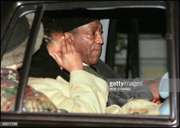 Actor Bill Cosby leaves his New York City home accompanied by his wife Camille and a young woman with her hands over her face believed to be one of...