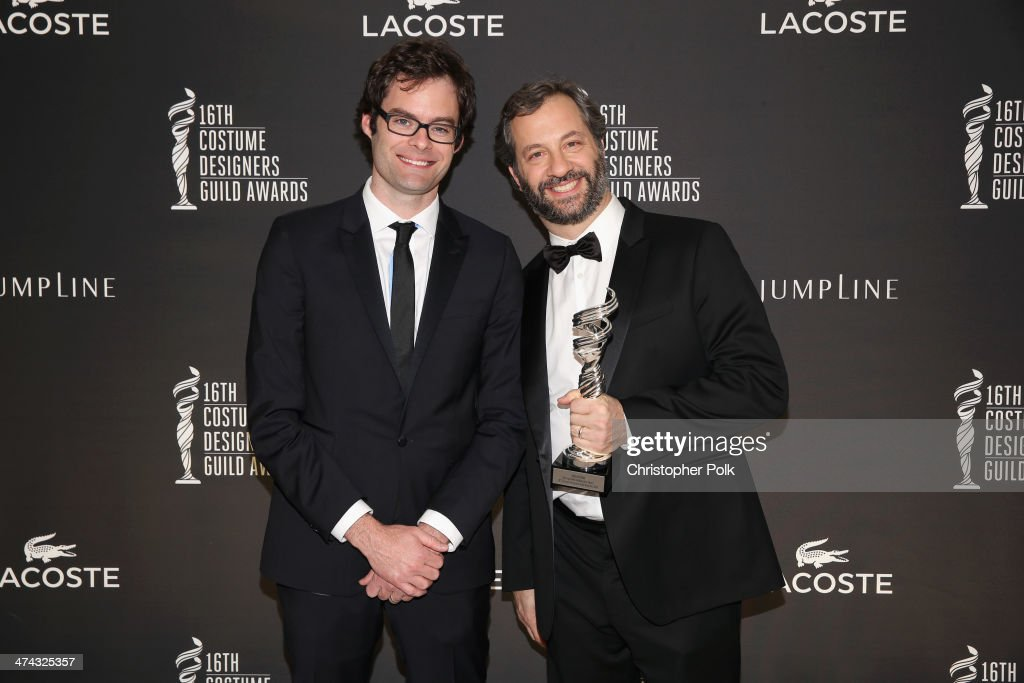 Actor Bill Hader and honoree Judd Apatow pose with the Distinguished Collaborator award during the 16th Costume Designers Guild Awards with presenting sponsor Lacoste at The Beverly Hilton Hotel on February 22, 2014 in Beverly Hills, California.