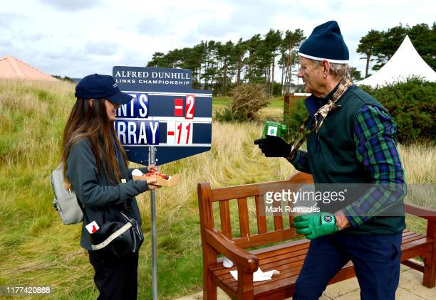 Actor Bill Murray hands the scorer a hot dog during Day two of the Alfred Dunhill Links Championship at Carnoustie Golf Links on September 27 2019 in...