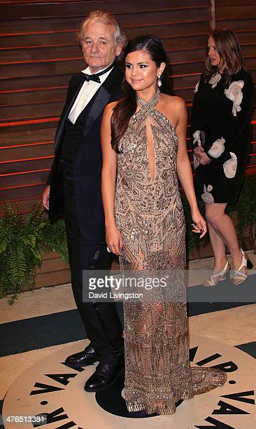 Actor Bill Murray photobombs recording artist/actress Selena Gomez at the 2014 Vanity Fair Oscar Party hosted by Graydon Carter on March 2 2014 in...
