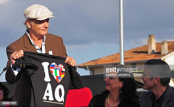 "Actor Bill Murray shows a tee-shirt ""I love L'Aquila"" to his colleague George Clooney during the opening ceremony of the ""Nobel for Peace"" cinema at..."