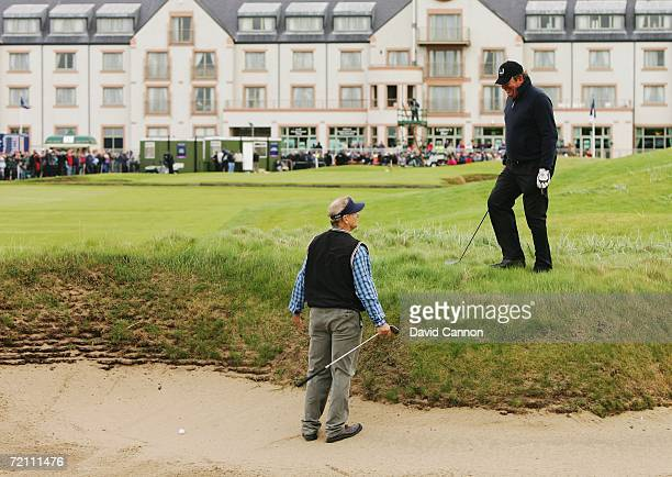 Actor Bill Murray takes advice from fellow competitor Johann Rupert before playing out of a bunker on the 18th hole during the Third Round of The...