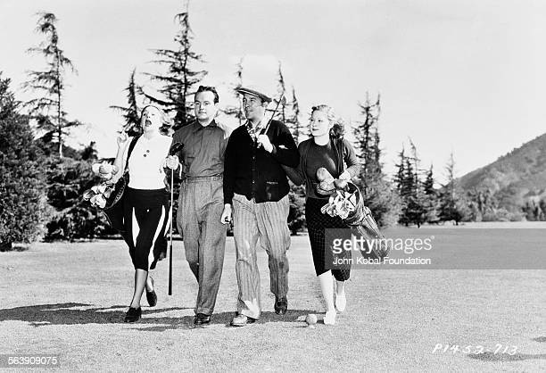 Actor Bing Crosby and entertainer Bob Hope walking arm in arm with their wives on a golf course for Paramount Pictures 1940